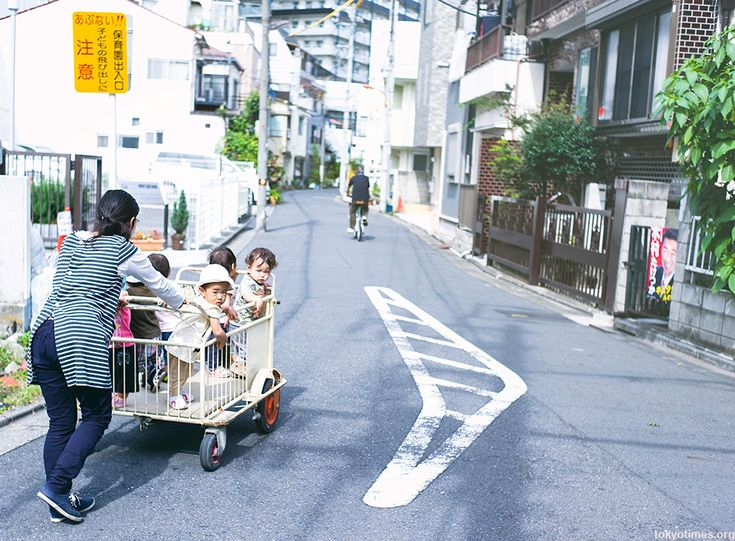 Japanese kids being pushed about in a cage or cart by lee chapman