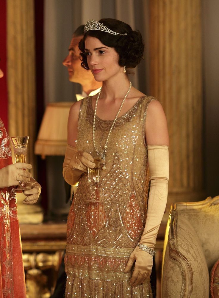 Downton Abbey (Christmas special season 4) - Janet Montgomery as Freda Dudley Ward wearing a beaded pink and champagne flapper dress, champagne satin opera gloves and diamond jewellery (a tiara, a bracelet, pendant pearl earrings and a necklace with drop pearl pendant).