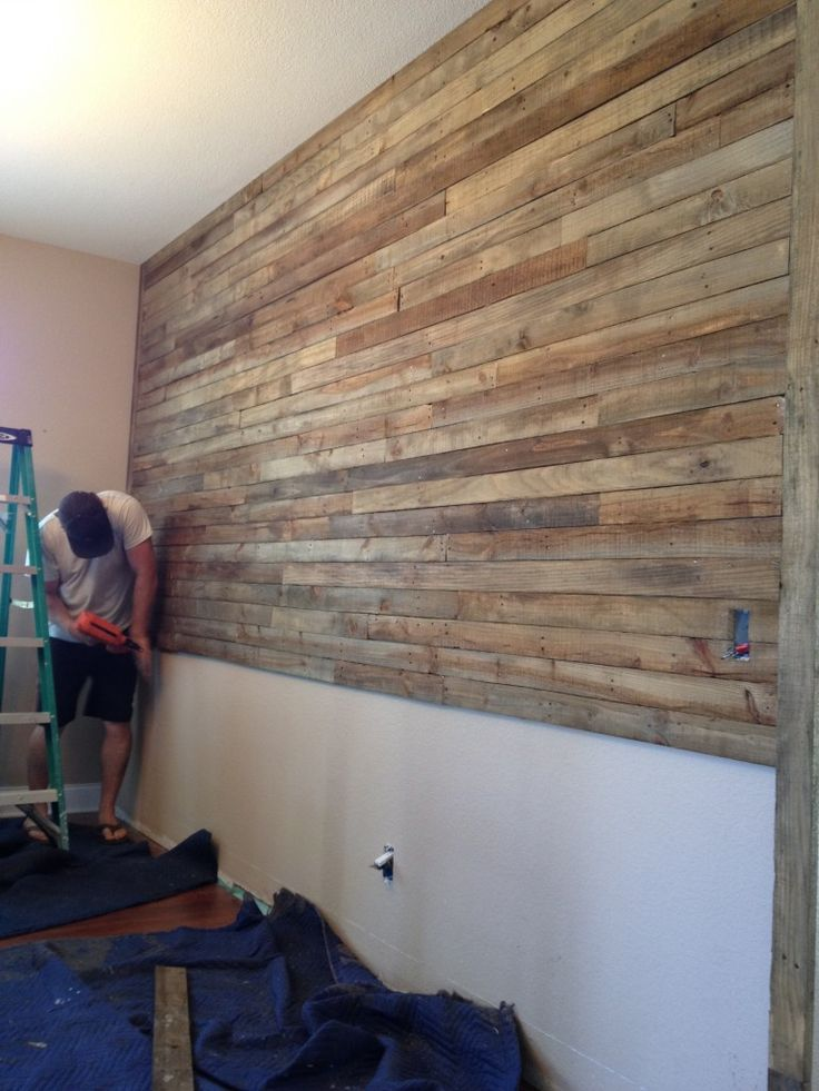 Wall made of reused wood pallets and stained with 1/4 mix of minwax walnut stain to 3/4 laquer thinner. Then nailed up with nail gun. Beautiful. This would look great in our fireplace room.