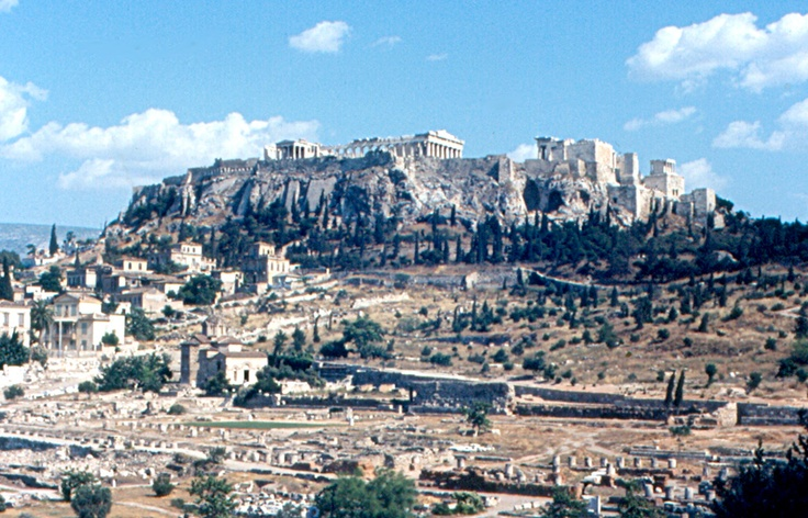 The Acropolis and Agora (market), seen from the Theseion in 1967. The Parthenon is in the center, and the Propylaea (main entrance) is at right. The photo is looking to the southeast.
