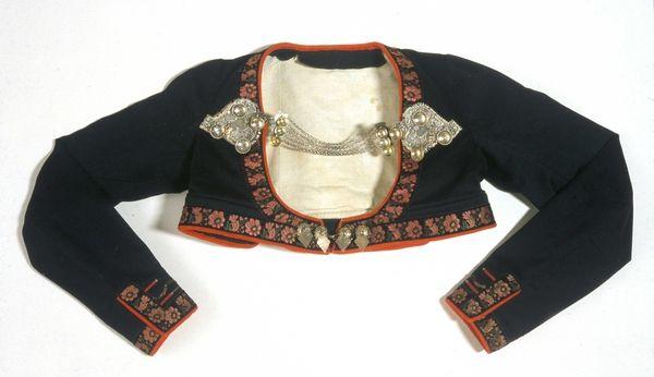 Mulig en del av Astrid Bakkes brudedrakt, fra Tinn i Telemark, da hun giftet seg i 1864. Trøye, skjæletrøye i svart klede, med dekorasjoner og et par filigrans trøyespenner og et par kulespenner.