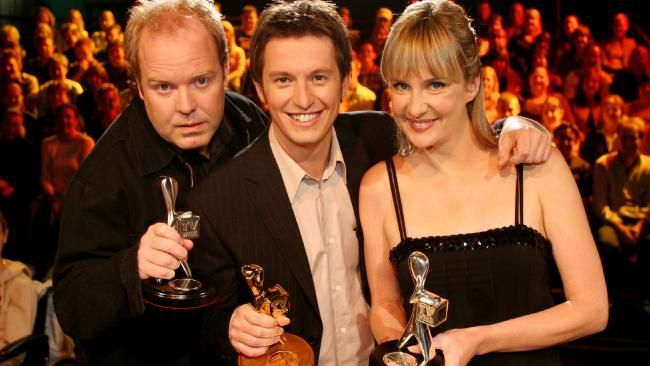Gold Logie winner Rove McManus flanked by colleagues Peter Helliar and Corinne Grant, with the three Logies he won for his show 'Rove Live' at the 2004 TV Week Logies.