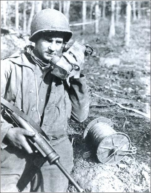 4th Infantry Division soldier armed with a M3 grease gun, talks on a field telephone. Hurtgen Forest, November 1944.