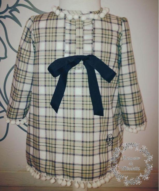 Vestido de cuadros con detalles de madroños en puños y bajo de la firma Cayetana Caudet