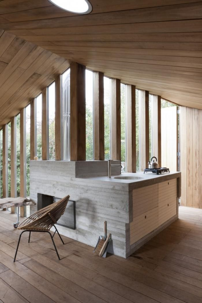 unique cabin design with wood and concrete interior.  wall of columns and windows with concrete kitchen/firplace