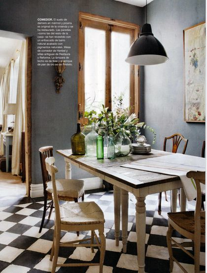 Industrial light fixture and wide-planked wood dining table, checked floor. Apartment decor.I am loving these slate-look walls.