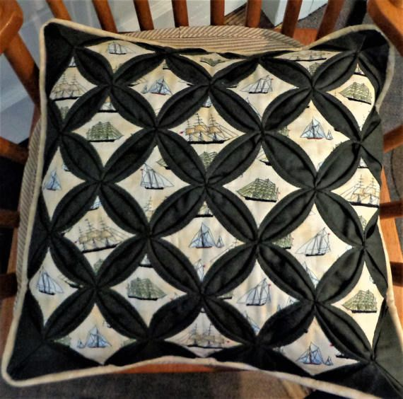 This is a handstitched pillow cover done in the cathedral window technique. Fabric squares featuring various sailing ships are stitched into dark dusty green fabric. A mottled beige fabric binds and backs the pillow cover.  The cover is 16 inches square and will fit a standard pillow form of those dimensions. The COVER ONLY is for sale, in order to limit shipping costs. Pillow forms can be purchased at most craft supply stores as well as online. For more info on buying a pillow form please…