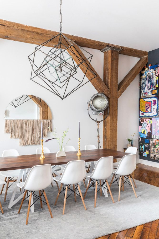 A statement making dining room with exposed wood beams and cool sculptural light fixture