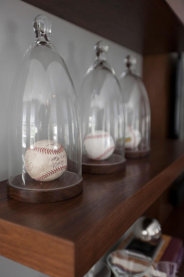 Designer Justine Sterling's client has loads of sports memorabilia and having these glass cloches made the perfect display for his signed baseballs.