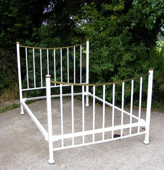 """An exquisite antique brass and iron double bed White painted simple classic design    Lovely curved brass top rail  to head and foot board  Comes complete with original side rails  Fits a standard UK Double Size mattress 4' ft 6 """" Wide x 6' ft 3""""  Long  or 137 cm x 190cm  Bed measures approx;   Headboard 135 cms High   Foot board 105 cms High   140 cms Wide   205 cms Length"""