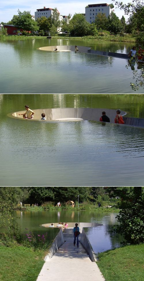 Observation deck below water-level in Vöcklabruck, Austria - photo by Roland Barthofer;   Visitors are able to sit in the middle of a pond without getting wet. The scenic landscape includes a path leading down to a hollowed out circular area where people can take a seat and relax. The ramp to the observational platform gradually descends as the water level gains height either side. To others, visitors like they're wading in the lake without a drop of water on them.