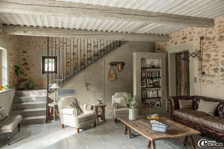 Dans le salon de la maison d'hôtes de charme, 'La Bergerie de Nano', table basse en bois sur tréteaux, canapé en cuir effet vieilli et fauteuils en lin naturel, le tout chez 'Flamant'. Porte en bois sur mesure, 'Portes Anciennes' à Saint-Rémy-de-Provence