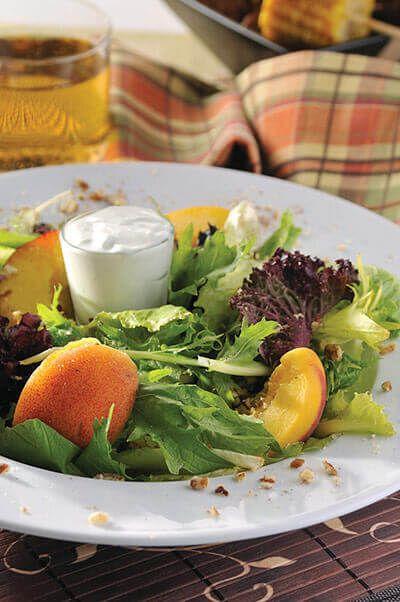 Aprovecha la temporada de duraznos y los diferentes tipos de lechuga para preparar una fresca ensalada acompañada de un aderezo de yogurt y queso azul.