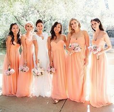 Peach bridesmaid dresses with nude sandals and white flowers of some sort.