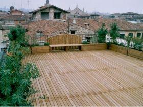 Pavimentazione ed arredo con fioriere e pannelli grigliati in legno di pino su terrazzo.
