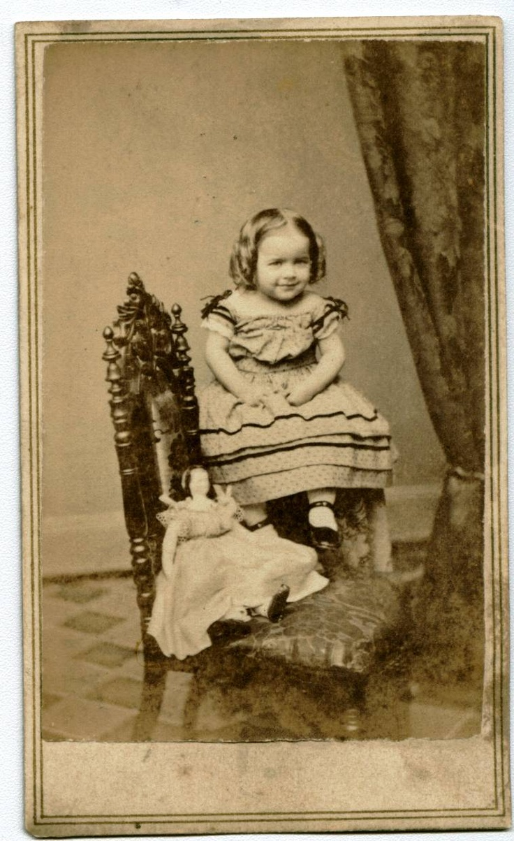 Antique photo of adorable little girl with her doll circa 1870.