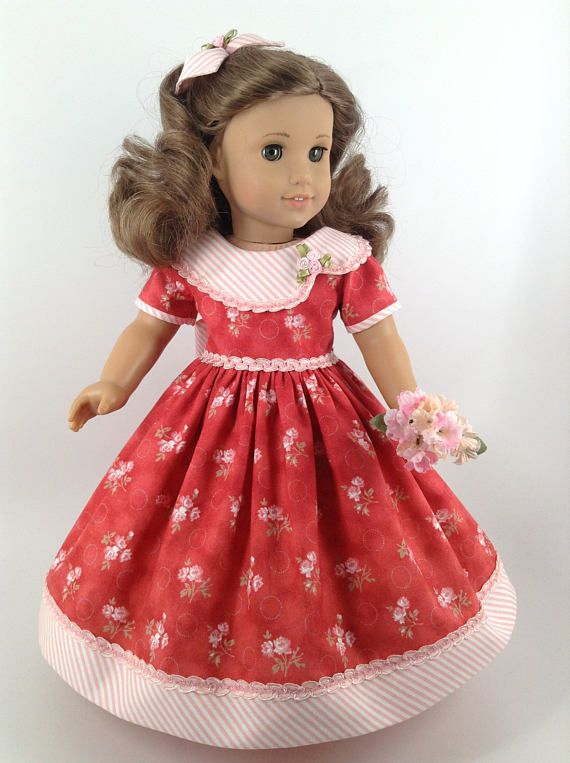 Handmade gown, petticoat, and hair bow for American Girl and other similar 18-inch dolls. Rebecca is modeling a pretty cotton gown with multi-colored pink and white flowers, green leaves and stems, and tiny dotted, barely visible green circles on salmon-red. Dress features include a lined bodice, slightly scooped neckline, a large collar in a coordinating pink and white striped fabric and accented with two-toned pink trim and ribbon flowers with pearl centers, standard sleeves banded in…