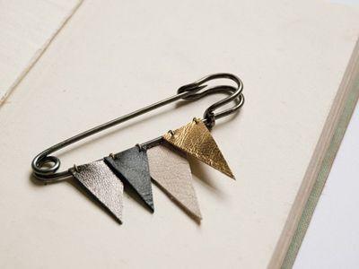Metallic leather brooch.
