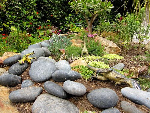 Dino garden. Hide dinosaurs or diggers/construction site style in one of the planting areas.