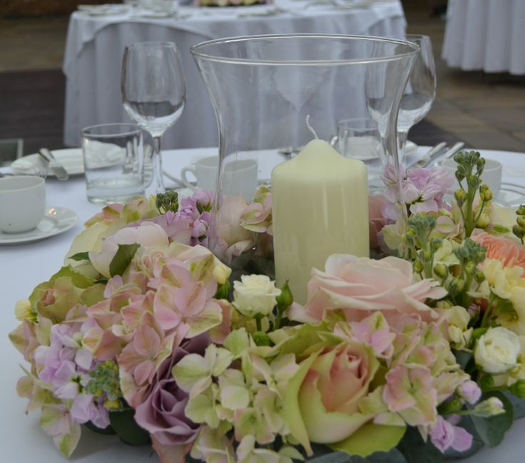 Hurricane lamp table arrangements with candle surrounded by a ring of flowers containing sweet avalanche and avalanche, memory lane and vendella, keira  and Juliet roses, stock and hydrangea - Northbrook Park