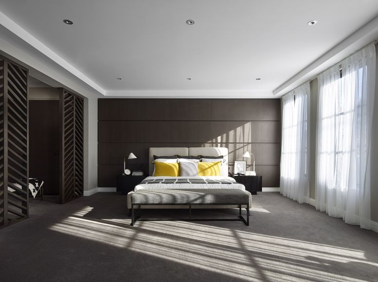 MASTER BEDROOM: This monochromatic master suite is awash in elegant grandeur and fashionable refinement. A palette of warm grey coats the space in serenity whilst shots of colour in the bed pillows maintain the energy level.   Visit High Street on our Lookbook here: http://www.metricon.com.au/get-inspired/lookbook/high-street