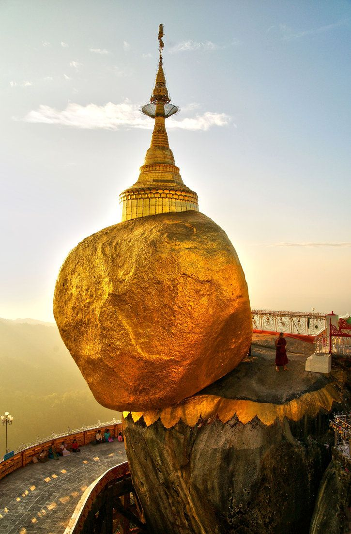 """With its great weight balanced so precariously on the cliff edge. According to legend, it is kept in place by a single hair of the Buddha.  Perched atop a cliff near Yangon, is one of the most sacred sites in Burma.  An endless stream of pilgrims come to admire the sight and add squares of gold leaf to its surface."""