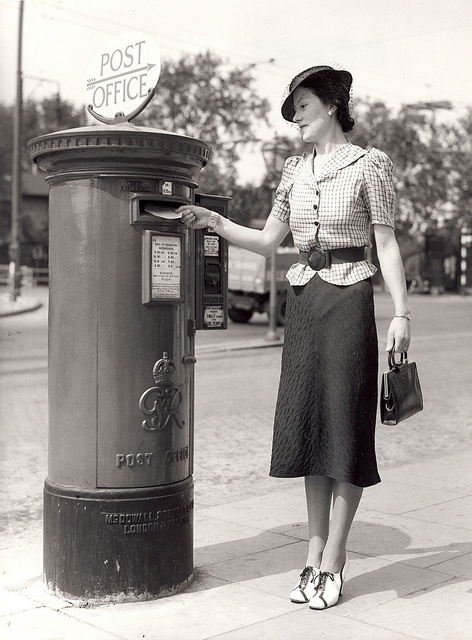 A lady posts a letter into a King George VI Pillar Box 1938