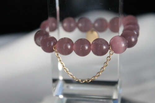 Purple beaded bracelet on stretchy elastic with dangling golden chain and round charm