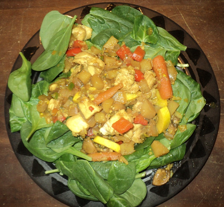 Curried chicken & veggies on spinach bed