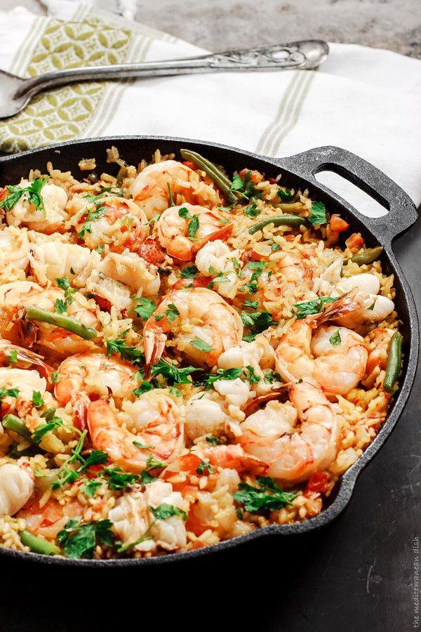 Easy Seafood Paella Recipe from The Mediterranean Dish! Step-by-step pictures will guide you as you make this all-star paella! You will fall in love at first bite! Pin it now.