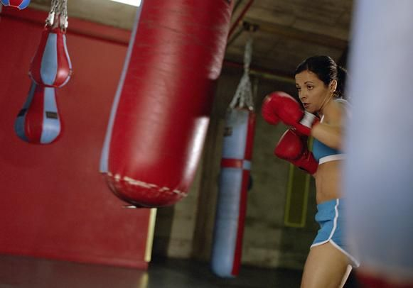 Boxing workout with a heavy punching bag to lose belly fat