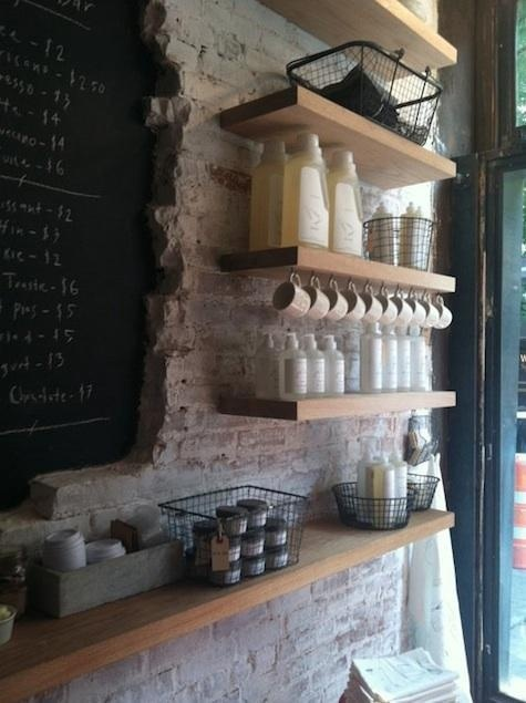 There's a lot here to love: exposed chalkboard underneath a white-wash (faux?) brick wall, natural wood shelving.