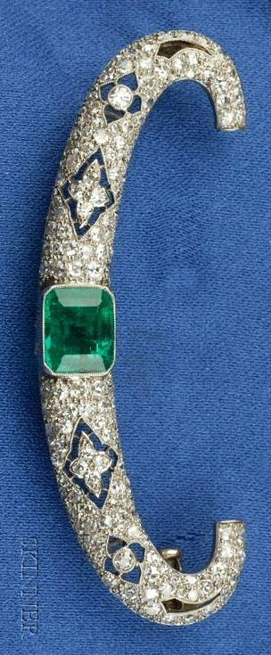 Art Deco Platinum, Diamond and Emerald Brooch the openwork form bezel-set with an emerald-cut emerald measuring approx. 8.19 x 7.88 x 5.57 mm, further bead-set with old single and old European-cut diamonds, millegrain accents, lg. 2 1/4 in., (partial French import stamp).