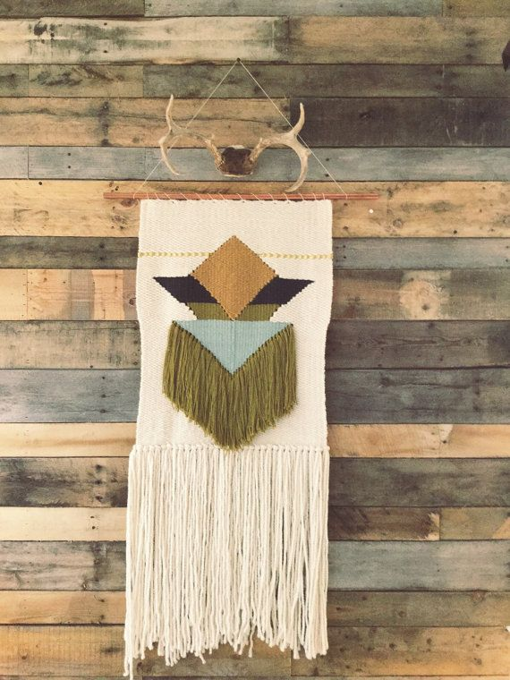 Handmade woven wall art in ivory, gold, olive green, light blue, navy, and with vintage gold ribbon. Hung in a 30 copper pipe, this weaving measures 50