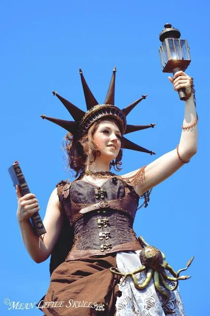 Steampunk Statue of Liberty Cosplay (corset, skirt, harness, torch, crown, book) - For costume tutorials, clothing guide, fashion inspiration photo gallery, calendar of Steampunk events, & more, visit SteampunkFashionGuide.com