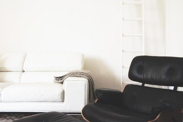 FASCINO COUNTRY: IL SOGGIORNO La zona soggiorno vede affiancati un divano in pelle bianca e una poltrona Lounge Chair di Vitra, design Charles & Ray Eames. Alle spalle, una piccola scala a pioli, eredità del vecchio casolare.