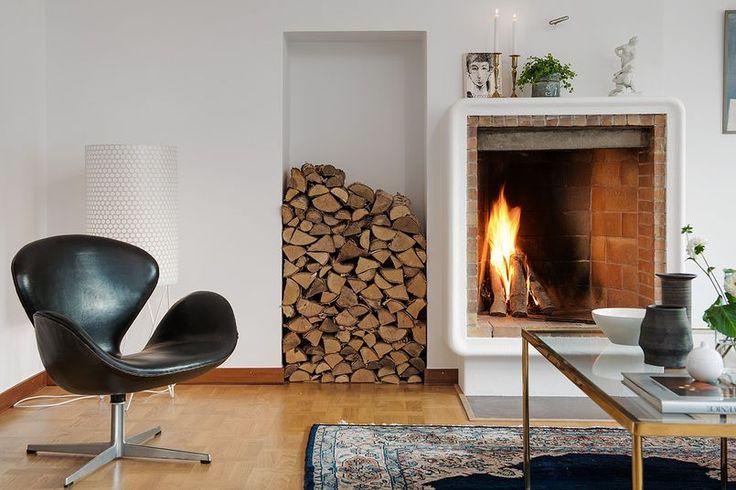 Prosty kominek z otwartym paleniskiem wyłożonym cegłą stanowi przytulne centrum tego salonu. Sąsiadującą z nim wnękę przeznaczono do przechowywania polan drewna, które stanowią naturalną ozdobę wnętrza. Perski dywan, klasyczny fotel obrotowy Swan, zaprojektowany przez Arne Jacobsena i elegancki mosiężny stolik ze szklanym blatem tworzą smaczny eklektyczny wystrój pokoju.
