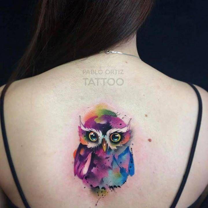 Tatuaje de un búho de estilo acuarela en la espalda.