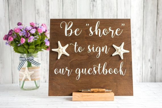 Remind your beach wedding guests to leave you a note with this Be shore to sign our guestbook sign adorned with real starfish! This super cute nautical sign is sure to look fantastic on your guestbook table, and it comes with its own stand so its ready to use.  This sign measures 11.5x11.5 and is made from birch plywood. The text and starfish are positioned slightly above center so none of the text is cut off when you slide the sign into the accompanying stand. The stand is a piece of solid…