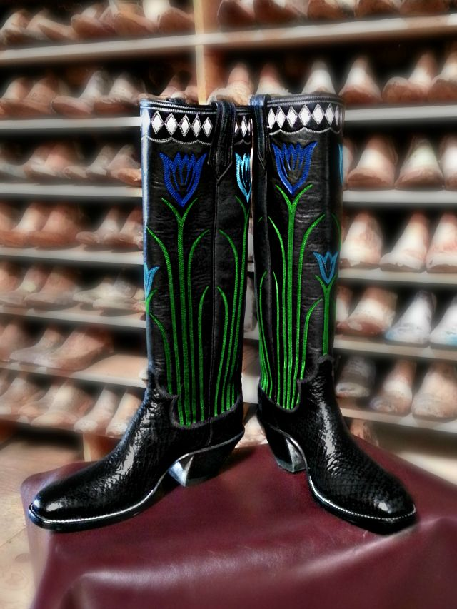 """Boot of the Month April 2014  17B """"The Tulip"""" April's custom cowboy boots of the month are ready to take you to any spring events, whether it's for work, dress, or play.  The 20"""" round  tops come in a black calfskin & are adorned with stitched tullips in blue and green. They are topped off with an inlaid collar of white diamonds.  The black sharkskin compliment the black tops. Shown with a custom French toe and a #4 heel. http://paulbondboots.com  Nogales, Arizona"""