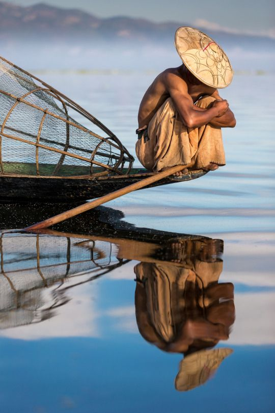 """A Burmese fisherman rests at the point of his boat on an Inle Lake morning in Myanmar"