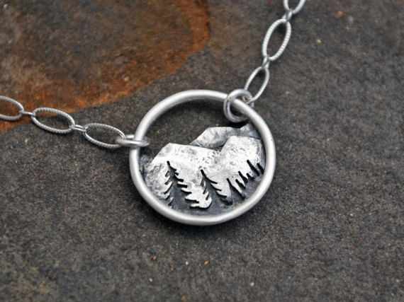 This little pendant features a rocky mountain range with a silhouetted tree line. It is all sterling silver and completely fabricated by hand with