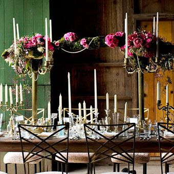 One tablescape design features a large mossy oak limb, draped with ranunculuses and pearls, suspended between two large candelabras holding arrangements of Pink Mink proteas, jasmine, hydrangeas, camillias, roses, pieris buds, and hyacinths. Vintage bottles and candlesticks scattered down the middle of the table complete the eclectic look.