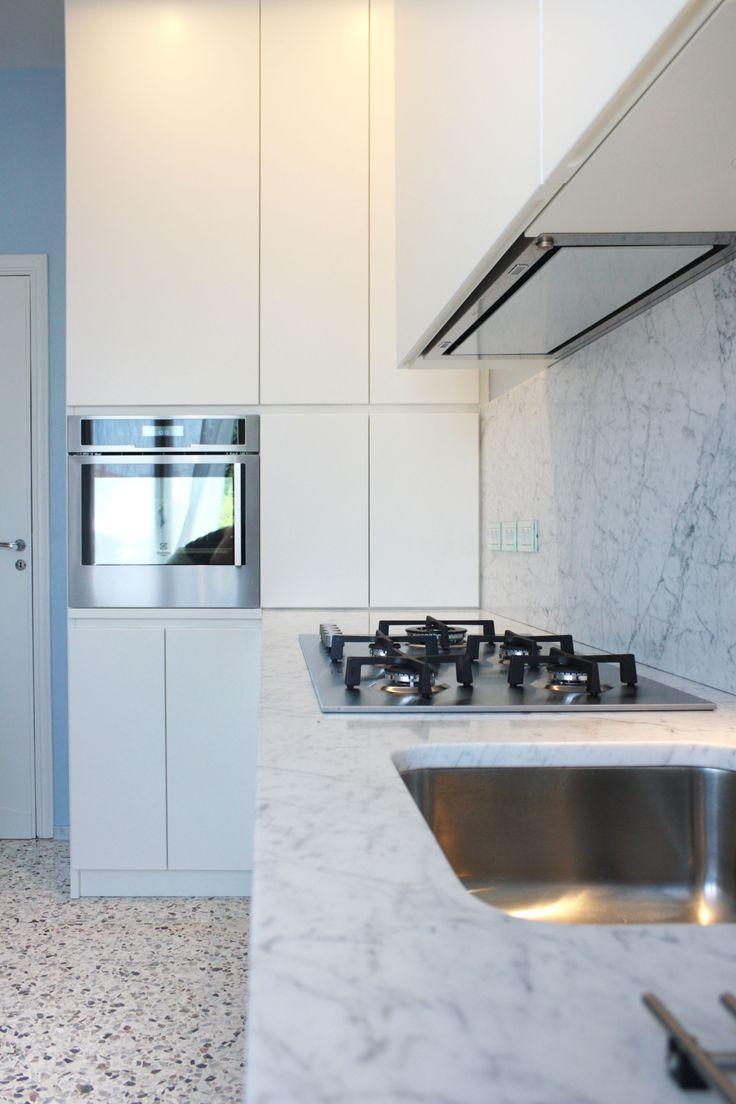 Nuova cucina in legno laccato bianco opaco, top e alzata in marmo bianco carrara. La pavimentazione esistente in graniglia è stata conservata e restaurata. Progetto #flaviabenigniarchitetto