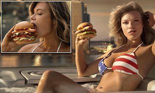 The 24-year-old beauty smolders in the commercial as she chows down on the the fast food chain's new Most American Thickburger, which is topped with a split hot dog and kettle chips.