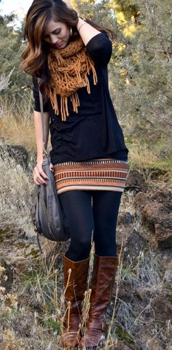 Black sweater with printed skirt, tights, boots, and infinity scarf.
