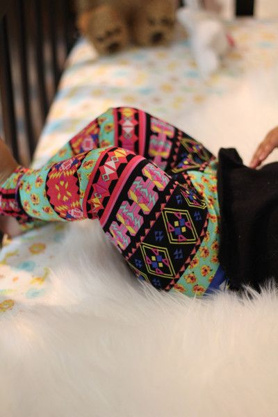 Toddler girl legs in crib wearing colorful Aztec fall leggings with tribal shapes