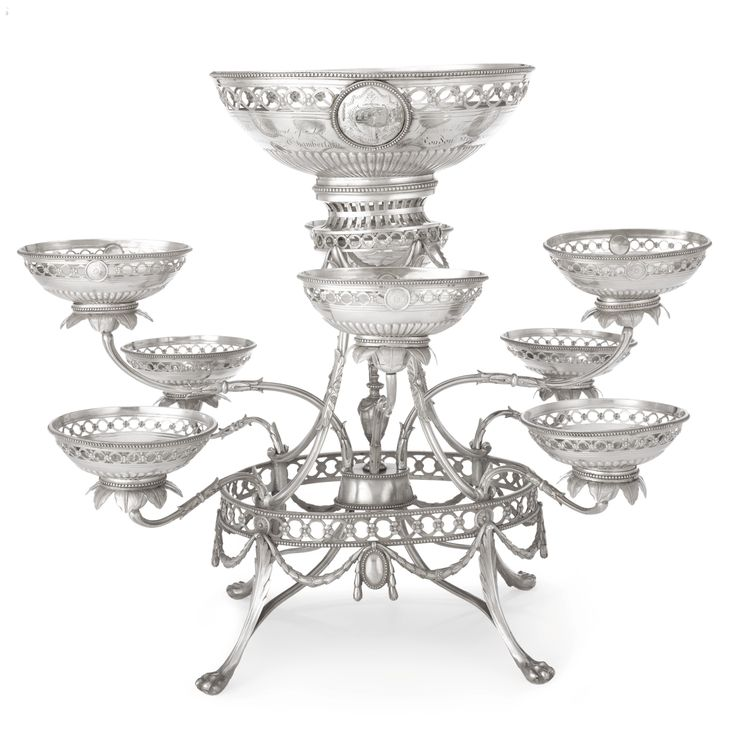 The London Company of Stationers: A George III Silver Nine-basket Epergne, Thomas Pitts, London, 1780 the oval frame raised on four paw feet headed by elongated leaves, linked by swags of husks and pendant beaded oval cartouches below a band of pierced rings joined by flowerheads, centered by an urn finial, the central oval basket with gadrooned lower body, the sides pierced to match