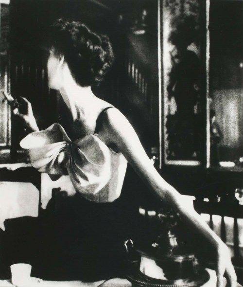 Photog: Lillian Bassman. Across the restaurant, 1949, shot at Le Grand Vefour, Paris, as part of assignments for Harper's Bazaar.  Model: Barbara Mullen. Dress: Jacques Fath.