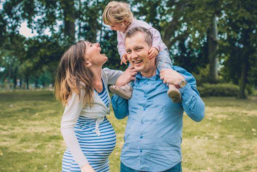 Séance Laetitia, Stéphane et Maëla, photo extérieur Bois de Vincennes, île de Reuilly et Île de Bercy, papa qui porte sa fille sur ses épaules avec maman qui rit